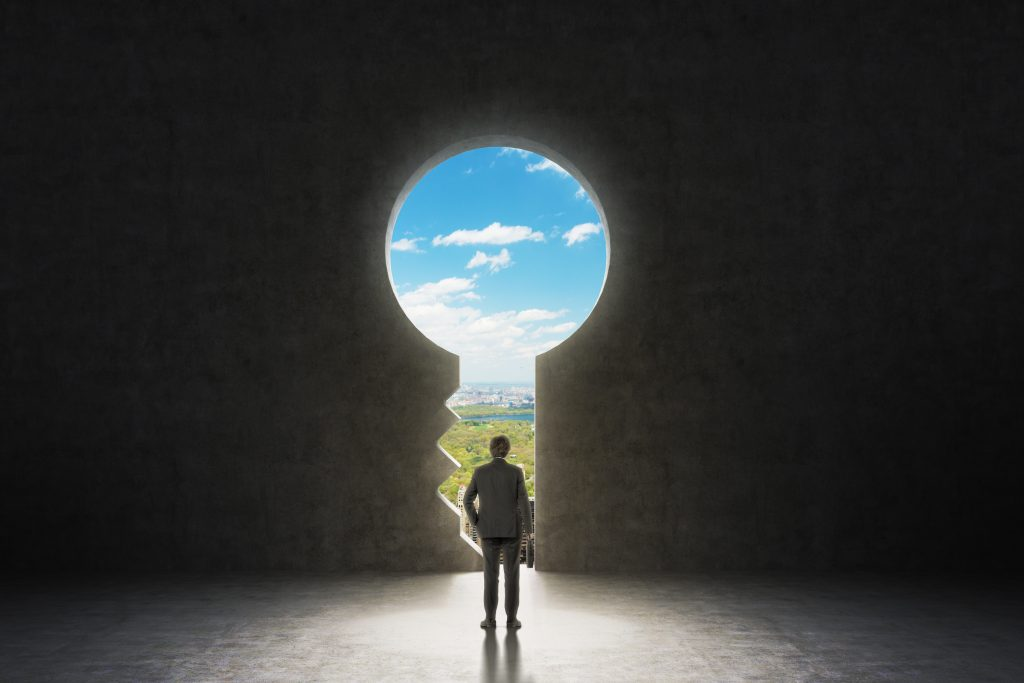 Business man looking out of a keyhole | Axiom Communications